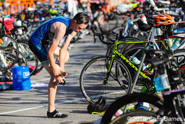 Racer attempts to put on socks with wet feet at the 2016 Tulsa Triathlon